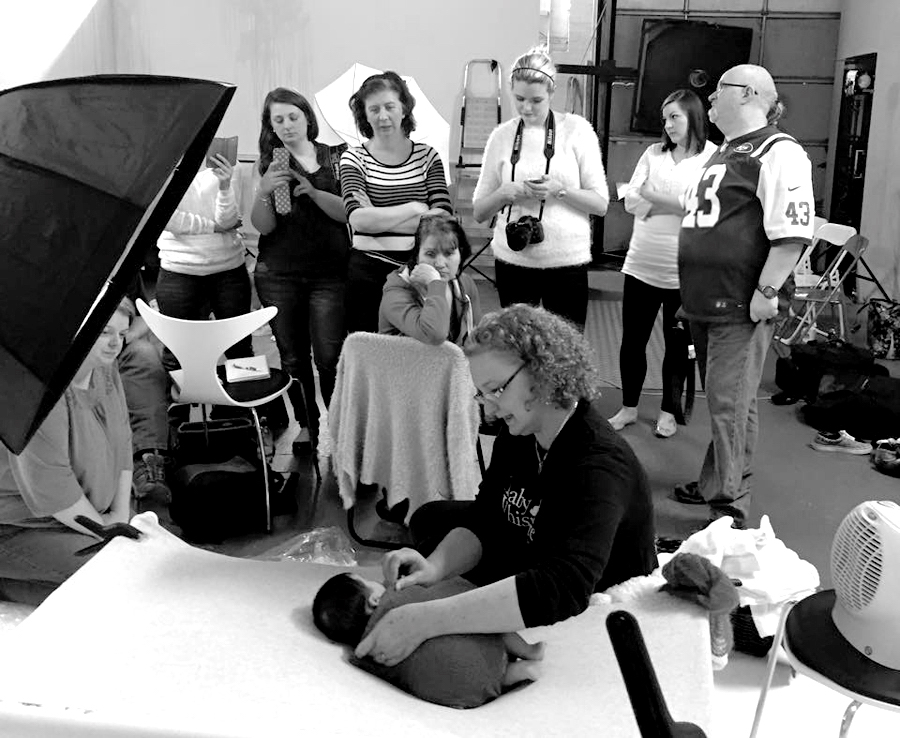 This is a behind the scenes image showing Jocelyn Conway teaching on a newborn photography workshop